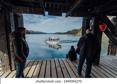 Bariloche, Argentina - April, 28th, 2019: Three men sheltered waiting for a boat at a pier in Villa la Angostura, with an incredible view of the glacier lake.