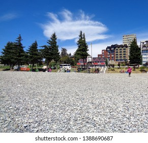 Bariloche/Argentina - February 9, 2017: a beautiful view from the stoned beach to the city, with a singularly shaped cloud. On the red plate, on the left: chocolate factory / on the right: handmade.