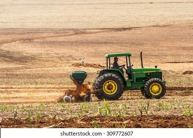 Bariri, Sao Paulo, Brazil, October 10, 2008. Tractor and fertilizer spreader in sugar cane field in Brazil