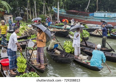 Barisal, Bangladesh - July 12, 2016: Two men standing in boats, negotiating the sale of bananas at the floating vegetable market