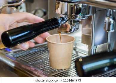 The barist pours coffee into a plastic cup