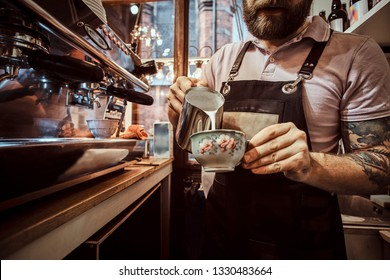Barista in apron making a cappuccino, pouring milk in a cup in a restaurant or coffee shop