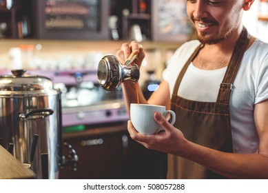 barista in apron pouring coffee into a small white cup