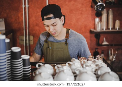 Barista asia preparing cup of coffee for customer in coffee shop.