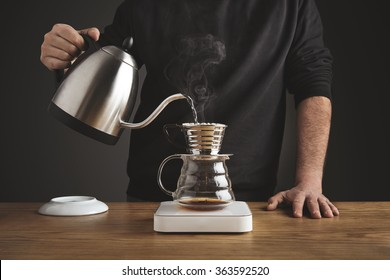 Barista black sweatshirt spills hot water prepare filtered coffee from silver teapot to beautiful transparent chrome drip maker on white simple weights. Everything thick wooden table cafe shop. Steam
