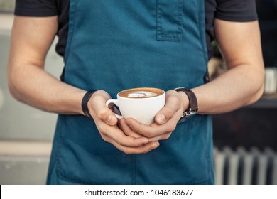 Barista in black t-shirt and blue apron holding  a cup of coffee with latte art
