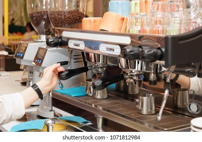 Barista is brewing coffee in a cafe using professional espresso maker