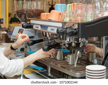 Barista is brewing coffee in a restaurant using professional espresso maker