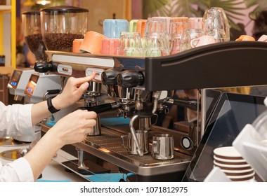Barista is brewing coffee using professional espresso machine