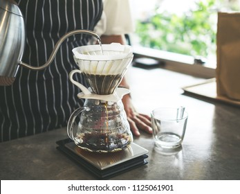 Barista Brewing Drip Coffee, Hand Pouring Hot Water from The Kettle over The Coffee Powder.