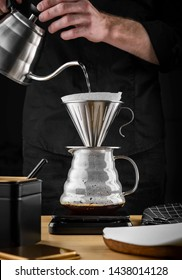 A barista brews coffee by an alternative method in pour over, coffee filter, glass teapot on a wooden tray on a dark background.