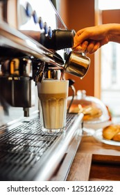 Barista in cafe or coffee bar preparing pouring espresso shot in glass of latte macchiato on espresso machine.