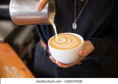 Barista carefully pouring a cafe latte coffee drink at a coffee shop featuring artisan drinks and food.