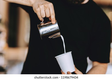 Barista carefully pours the milk into a glass in a modern coffee shop.