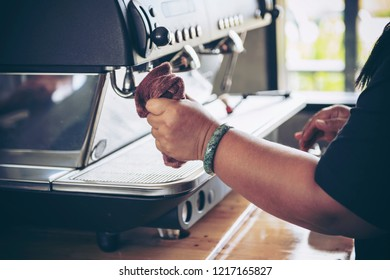 Barista cleaning coffee machine at coffee shop.