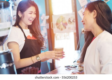 Barista coffee holding cup of coffee service to customer with blurry background - young attractive Asian female successful working in small business coffee shop