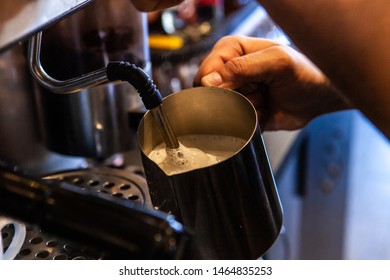 Barista froths milk in coffeehouse. A closeup view on the working hands of a coffeshop server, using a frother to create microfoam from warm milk, to be added into a cappuccino in a bistro.