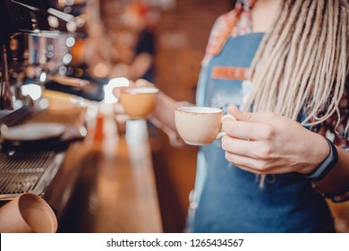 Barista girl with dreadlocks holds two small cups of espresso. She just made hot drink on coffee machine and is ready to serve guests