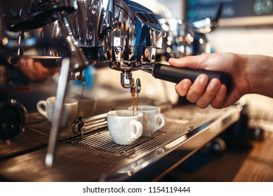 Barista hand pours beverage from coffee machine