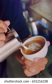 The Barista hands making a cup of coffee latte art.