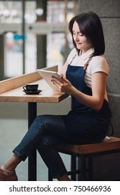 Barista having coffee break, she using tablet PC