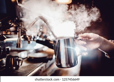 Barista heats milk with high-pressure steam for making lattes.