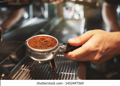 barista holding coffee holder with ground coffee near professional coffee machine preparing coffee drink in cafe close up