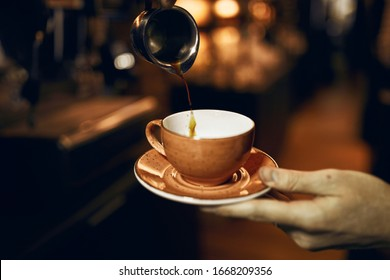 barista holding a cup with source pouring coffee in steel cup, close up cropped photo.good morning