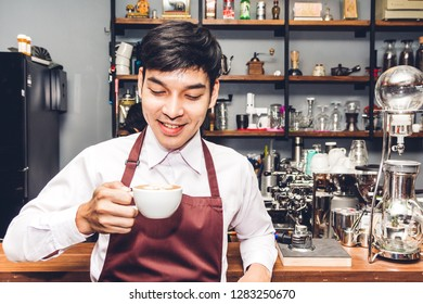 Barista holding and making coffee standing behind the counter bar.Man barista preparing coffee for customer in a cafe