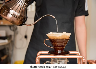 Barista holding pot pouring hot water to dripping coffee