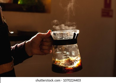 barista holds a drink in hand with a steam making alternative way of brewing coffee in the coffee shop hario v60 soft light background