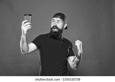 Barista job position. Cheerful barista. Man bearded hipster red cap uniform hold paper coffee cup. Barista recommend caffeine beverage. Coffee shop staff wanted. Barista prepared drink for you.