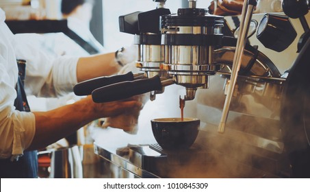 Barista make coffee latte art with espresso  machine in  cafe vintage color tone