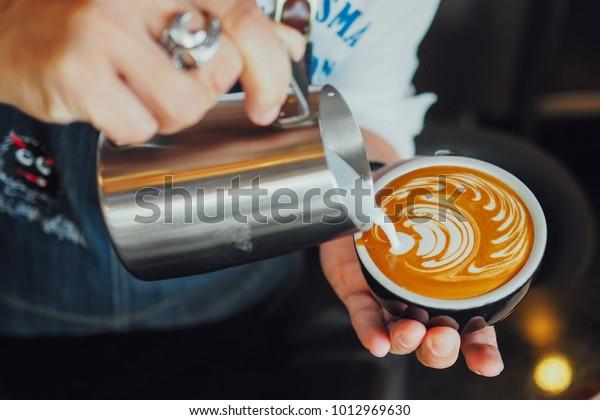 barista make coffee latte art with coffee espresso machine in coffee shop cafe in vintage color tone