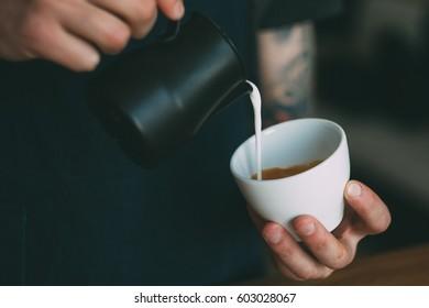 Barista makes cup of coffee. Barista makes cappuccino.