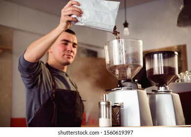 Barista makes espresso in cafe. Barista grind beans with coffee machine. Coffee grinder grinding roasted beans in powder. Fresh ground coffee in portafilter.