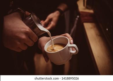 Barista makes flavored cappuccino, pours milk into coffee