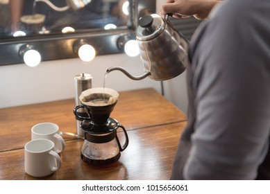 Barista making brew coffee by pouring water on ground coffee.