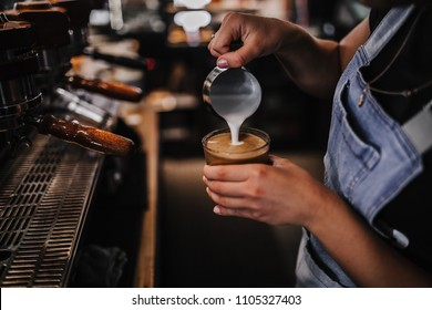 Barista making cafe latte in coffee shop, close up view on coffee