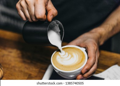 Barista making cappuccino with latte art. Close up of bartender hands prepares a coffee with a draw on foam. Specialty coffee