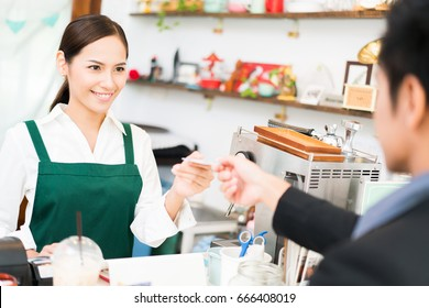 Barista is making coffee at his restaurant. and own a coffee shop she is swiping credit card. Where customers are paying