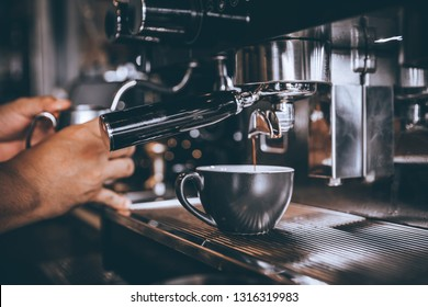 Barista making coffee with coffee machine in cafe.