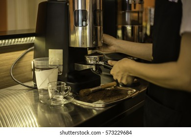 Barista making coffee with machine on counter