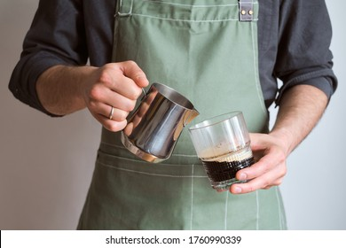 Barista making coffee. A man holds a milk jug and a glass of coffee. The guy makes cappuccino, pouring whipped milk into espresso. Barista in a kitchen apron. Equipment for professional service