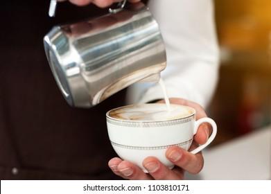 Barista making coffee. Pouring milk to cappuccino.