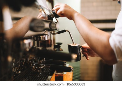 Barista making coffee using a coffee machine, hospitality and hot beverage concept, horizontal image, selective focus.