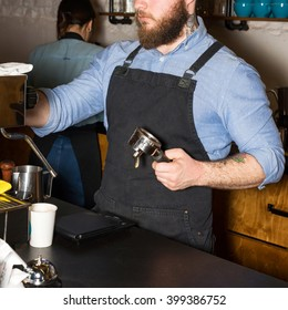 Barista making coffee using press for ground coffee