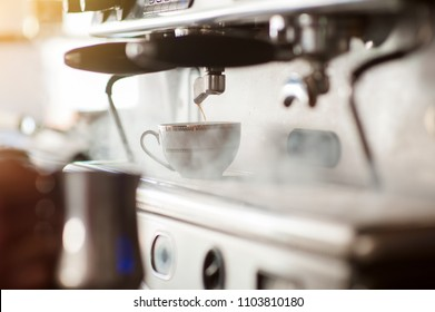 Barista making a espresso with a classic Italian coffee machine with steam in background.