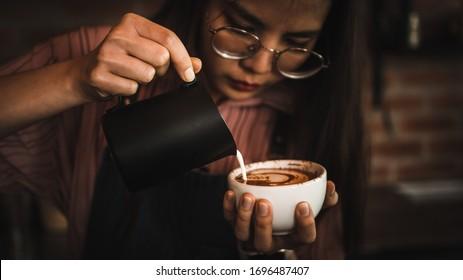 Barista making latte or cappuccino coffee pouring milk making latte art, retro filter effect