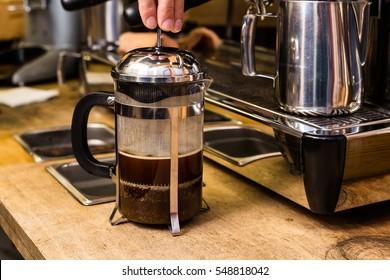 Barista making non traditional coffee in french press, barista coffee preparation service concept.